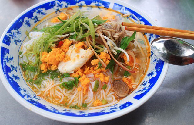 This rice noodle soup is served with broth covering noodle and topped with stir-fried fish meat with turmeric, shredded morning glory and water mimosa. Photo: Collection